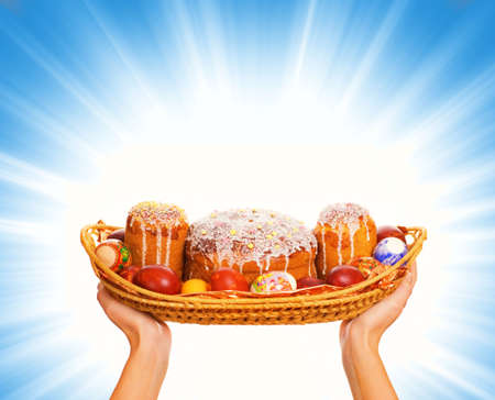 Hands holding woven basket full with easter eggs and easter cakes Stock Photo - 2339903