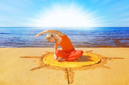 Beautiful girl meditating on the beach photo