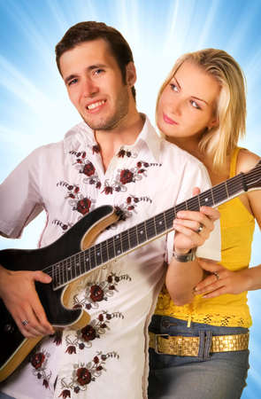 Young musician playing guitar, beautiful blond girl standing nearby Stock Photo - 2346525