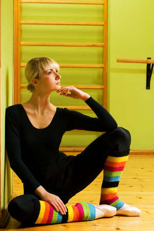 warmers: Beautiful ballet dancer sitting on a floor and relaxing after exercise