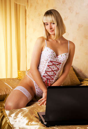 Young woman on a bed with laptop Stock Photo - 2378678