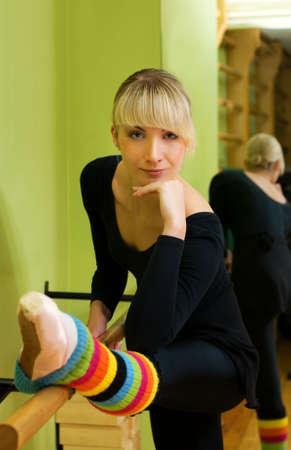 Ballet dancer doing exercise near the bar photo