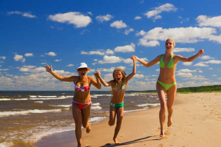 Mother and two daughters running on a beach near the water photo