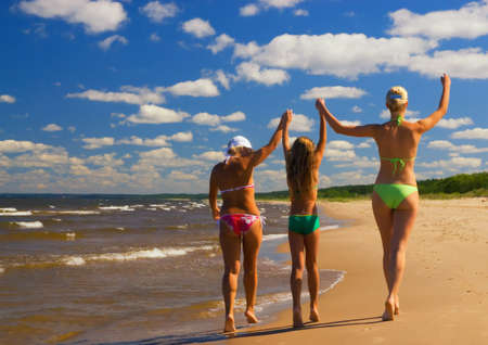 Mother and her two daughters walking on a beach photo