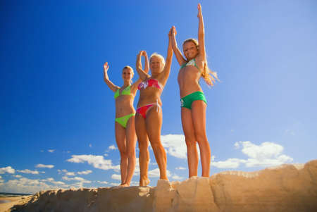 saluting: Mother and her two daughters stands on a beach with their hands up Stock Photo