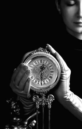 mystery woman: Monochrome picture of a beutiful girl with a clock (focus on clock) Stock Photo