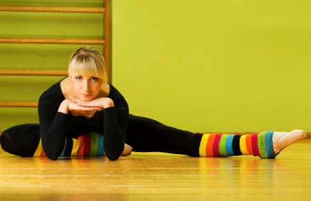 leg warmers: Ballet dancer doing stretching exercise on a floor