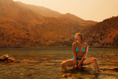 Beautiful young woman relaxing in water at sunset Stock Photo - 2457759