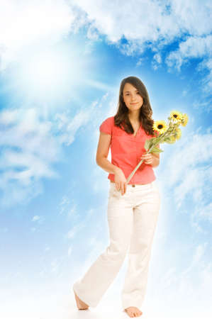 Beautiful teenage girl holding bunch of sunflowers isolated over blue cloudy sky photo