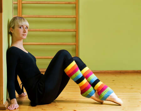 pointes: Beautiful ballet dancer sitting on a floor and relaxing after exercise