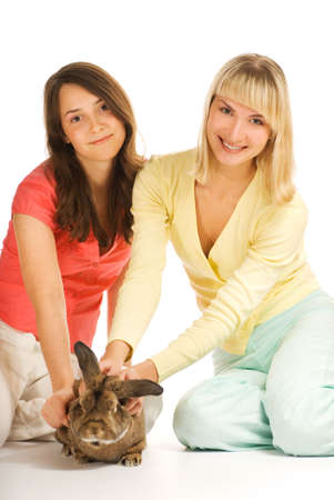 Two girls playing with bunny isolated on white background photo