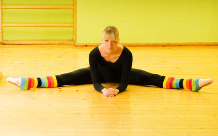 Ballet dancer doing stretching exercise on a floor photo