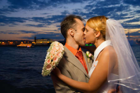 Just married couple kissing near the river at sunset time photo