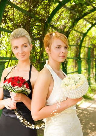Two girls with a flowers in green alley photo