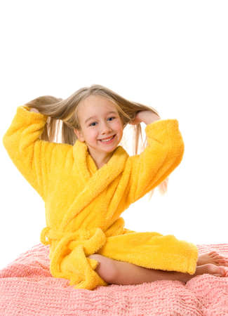 Pretty young girl sitting on a bed and touching her hair Stock Photo - 2671925