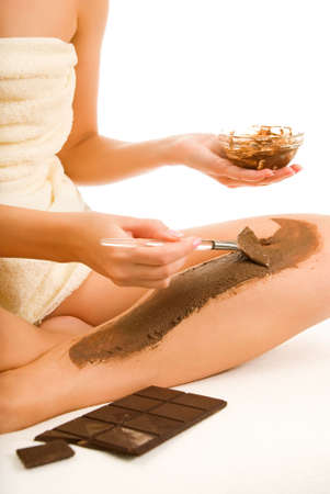 chocolate mask: Beautiful woman applying chocolate mask to her skin