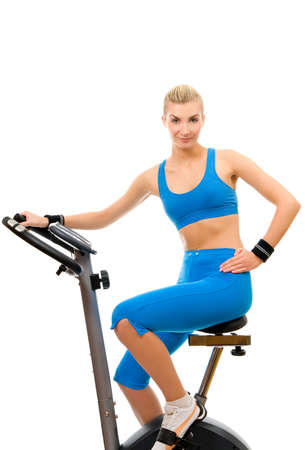 Beautiful young woman on exercise bicycle over white background photo