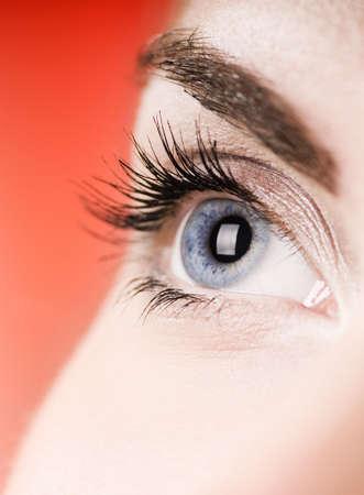 Blauw oog op rode achtergrond (ondiepe DOF)