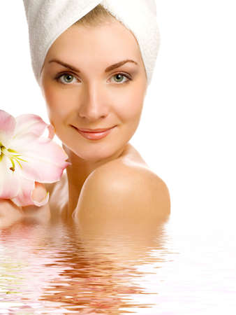Beautiful young woman with pink lily reflected in rendered water photo