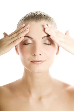 Beautiful young woman massaging her face photo