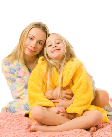 Mother and her daughter sitting on a bed photo