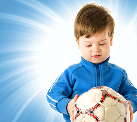Handsome boy with soccer ball over abstract blue background photo
