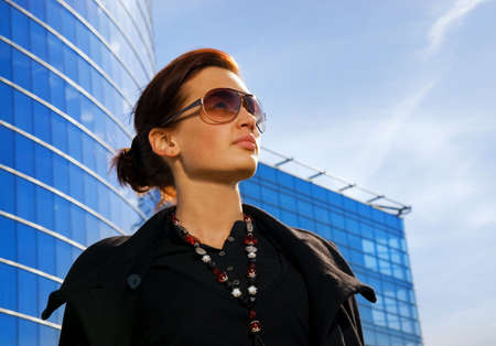 Beautiful young brunette. Modern building behind her Stock Photo - 2930365