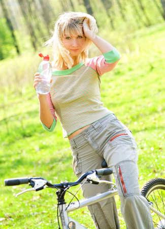 Beautiful young woman relaxing after riding a bike photo