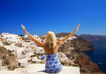 Blond woman with hands wide open sitting on a buildings roof. Santorini island (Greece) photo