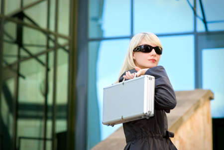 Beautiful young woman with silver case near the modern office building Stock Photo - 3674394