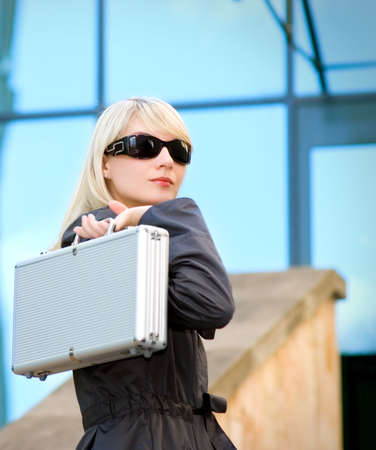 Beautiful young woman with silver case near the modern office building Stock Photo - 3674378
