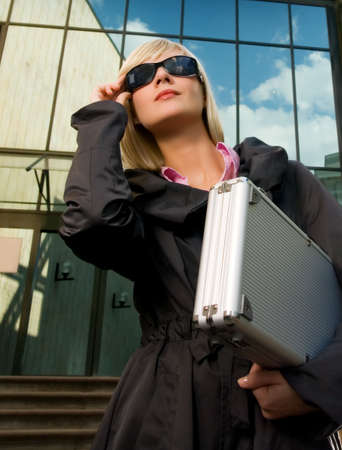 Beautiful young woman with silver case near the modern office building Stock Photo - 2948972