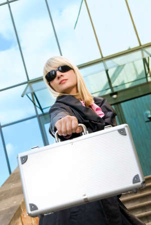 Beautiful young woman with silver case near the modern office building Stock Photo - 2948975