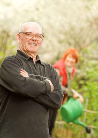 regando plantas: Feliz altos jardinero y la mujer regar las plantas sobre un fondo