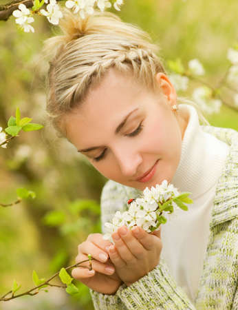 Beautiful young woman looking at ladybug on flowers photo