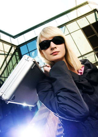 Beautiful young woman with silver case near the modern office building Stock Photo - 3048477