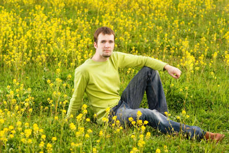 environmen: Relaxed young man sitting in a flower field