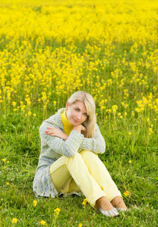 Beautiful young woman sitting in a flower field photo