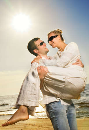Young happy couple having fun on the beach photo