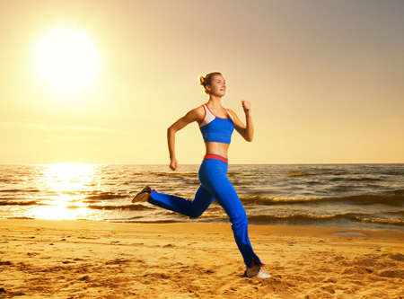 sudando: Hermosa joven corriendo en una playa al atardecer (tiro real, de fondo no es photoshopped)