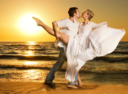 Beautiful young couple dancing tango on the beach at sunset Stock Photo - 3116348