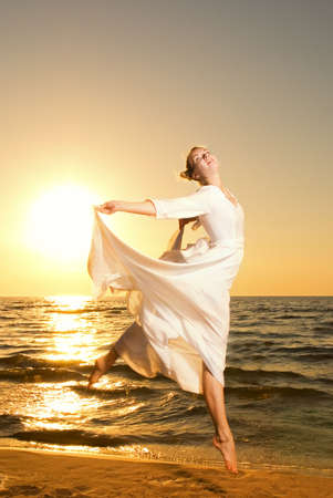 Beautiful young woman jumping on a beach at sunset Stock Photo - 3120267