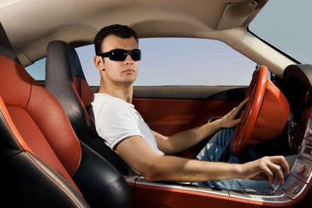 hombre conduciendo: Hermoso joven deporte moderno de conducci�n de autom�viles  Foto de archivo