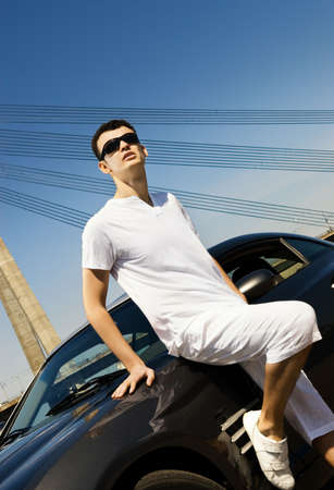 Handsome man standing near the modern sport car photo