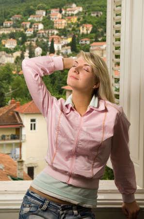 Beautiful young woman relaxing near the window photo