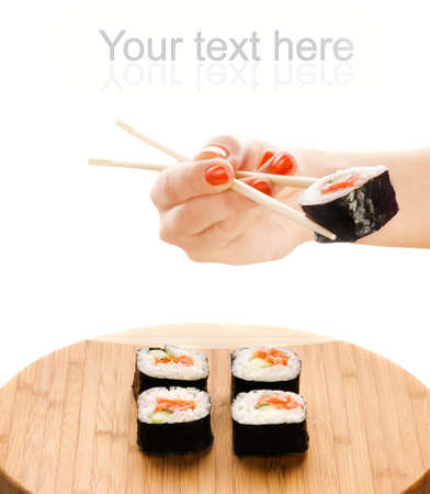 Hand holding sushi maki with wooden chopsticks photo