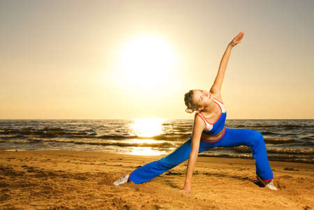 Beautiful young woman doing fitness exercise on a beach at sunset photo