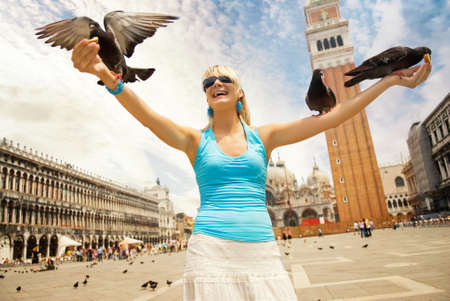 Beautiful young woman feeding pigeons photo
