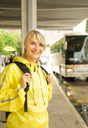 raincoat: Beautiful young woman waiting for the bus Stock Photo