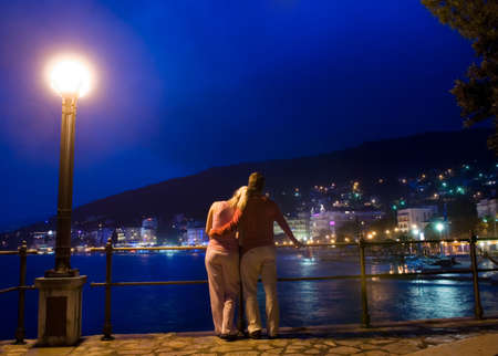 Couple standing near the sea and looking at night city panoram photo